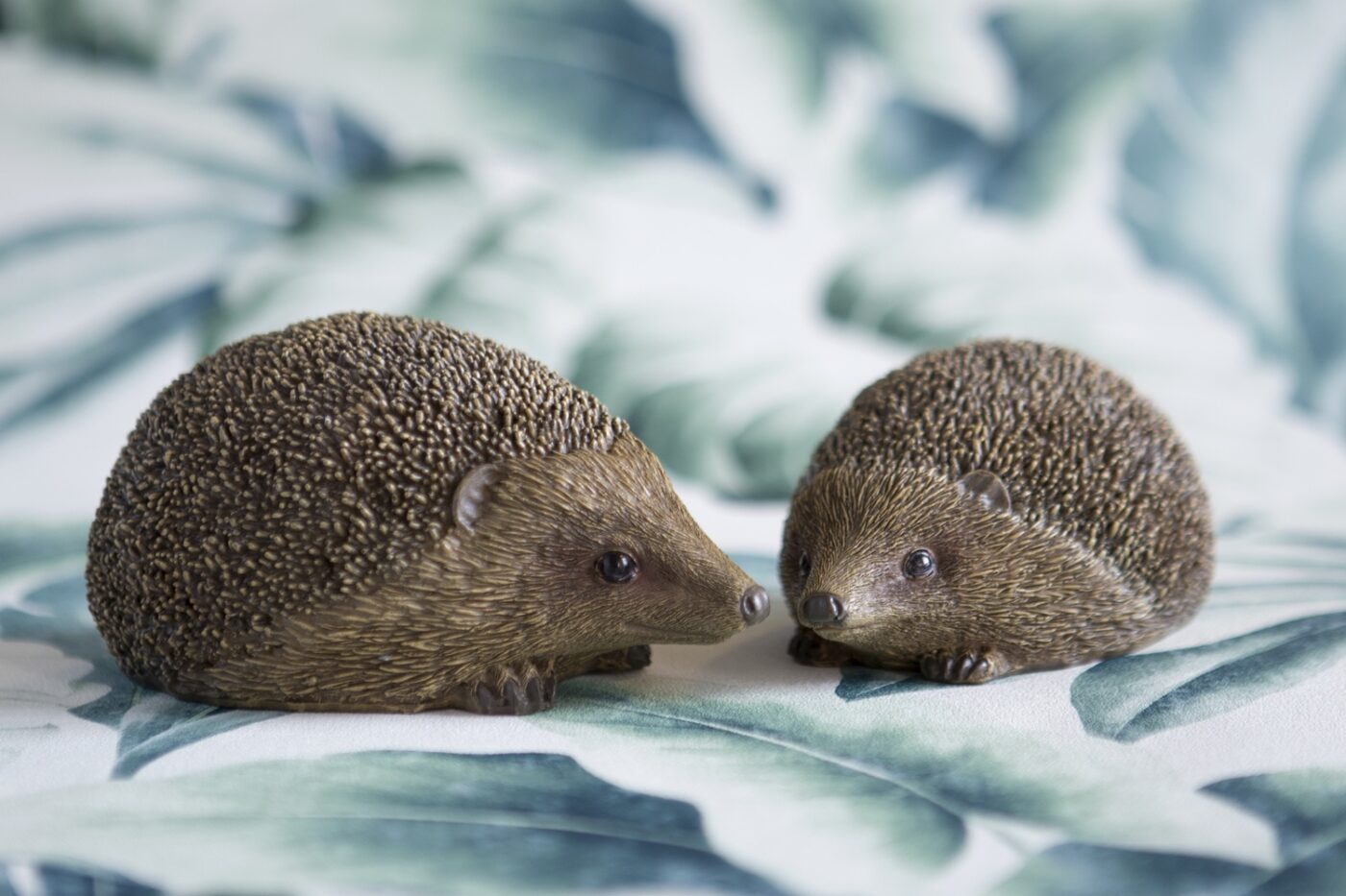a pair of small wooden hedgehogs